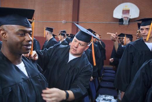 Darrington seminary extension graduate Trent Lantzsch (center) adjusts a fellow graduate's regalia before the first commencement in Southwestern Seminary's prison extension program. (SWBTS Photo/Matt Miller)